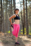 Young Fitness Woman Stretching her Legs in the Pine Forest. Female Runner Doing Stretches . Healthy Lifestyle Concept.