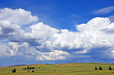 Cloudscape over rolling green hills