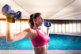 Muscular woman is training with weights dumbbells