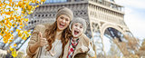 mother and child travellers in Paris, France showing thumbs up