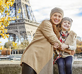 mother and child tourists embracing on embankment in Paris