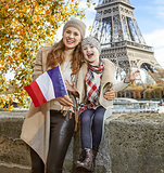 mother and child travellers showing flag on embankment in Paris