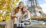 mother and child travellers taking selfie on embankment in Paris