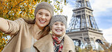smiling mother and daughter tourists taking selfie in Paris