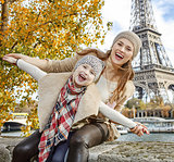 smiling mother and daughter travellers having fun time in Paris