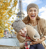 mother and child tourists on embankment in Paris having fun time