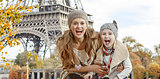 mother and child tourists having fun time on embankment in Paris