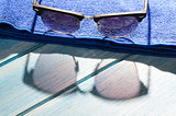 stylish sunglasses and towel on table