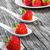 strawberries on a porcelain spoons on an old rustic table