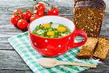 broth with vegetables, chicken meat and greens in the red soup c
