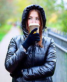 Girl in jacket with hood, holding a coffee or tea, young enjoys the outdoors and sports, spring  autumn, lifestyle, black , the concept of breakfast, gloves