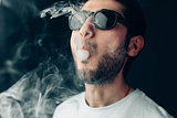 Young cool guy in sunglasses exhales a cloud of smoke. Studio horizontal portrait in close-up.