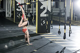 Athletic girl stands upside down in gym