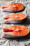 Three Raw Salmon Steaks on Parchment Paper