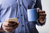 hands with smartphone and a mug