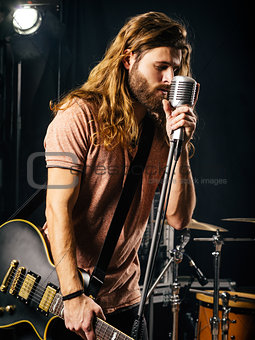 Young man singing and playing electric guitar on stage