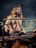 Young man with long hair playing drums