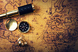 vintage compass and telescope on old world map. copy space
