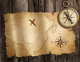 old nautical compass on wood table with treasure map