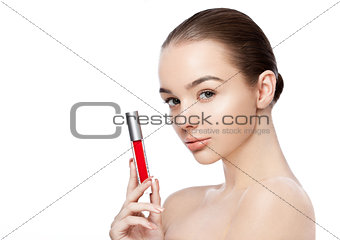 Beautiful girl holding liquid red lipstick