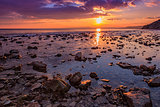 Exciting  rocky coast sunset with water reflection