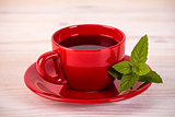 Red cup of tea with green leaves