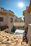 View among yellow houses on the roof tiles and second floors with towers. Spain.