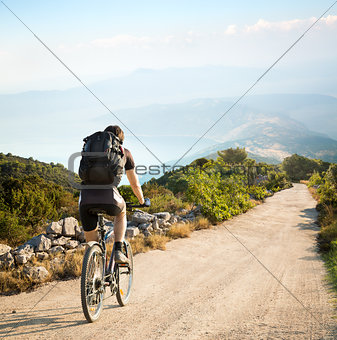 Man with Backpack Riding a Bicycle in Mountains