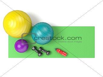 Fitness ball, dumbbells and plastic water bottle on green yoga m