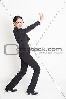 Asian businesswoman pushing something