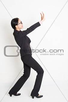 Asian businesswoman lifting something heavy