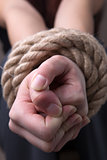 Tied rope hands of woman