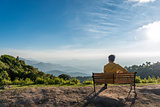 Traveler man siting wooden bench with Mountains