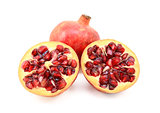 Whole red pomegranate and two cut halves showing seeds