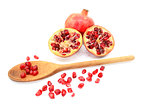 Pomegranate and two cut halves with seeds removed with spoon