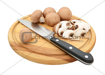 Knife with sliced and whole chestnut mushrooms on chopping board