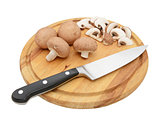 Knife with whole chestnut mushrooms and slices on board