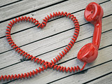 Phone reciever and cord as heart on white wooden background.