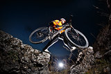 Athlete jumping across rocks with his bicycle