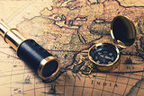 vintage compass and spyglass on old world map