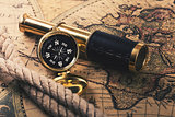 adventures concept - vintage compass and spyglass on old world m