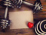 metal dumbbells and red heart on a wooden background