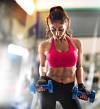 Muscular woman is training at the gym