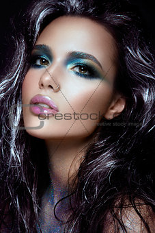 Beautiful girl with blue glitter on her face