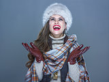 smiling trendy woman isolated on cold blue catching snowflakes