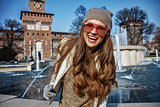 Portrait of happy trendy traveller woman in Milan, Italy