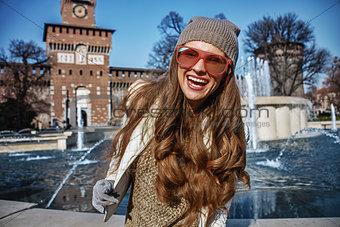 Portrait of happy trendy traveller woman in Milan, Italy