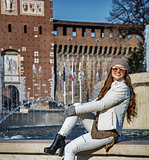 tourist woman in front of Sforza Castle sitting near fountain