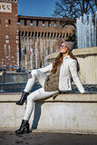 trendy woman in Milan, Italy sitting near fountain
