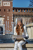 happy woman near Sforza Castle in Milan, Italy looking at map